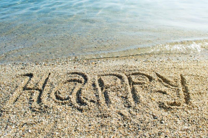 Счастливое слова написанное на пляже стоковое фото