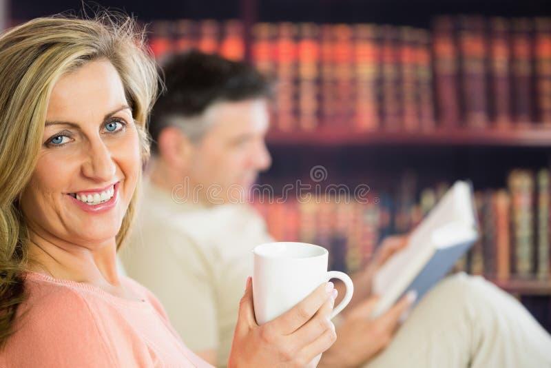Счастливое чтение пар и выпивая кофе в читальном зале стоковая фотография rf