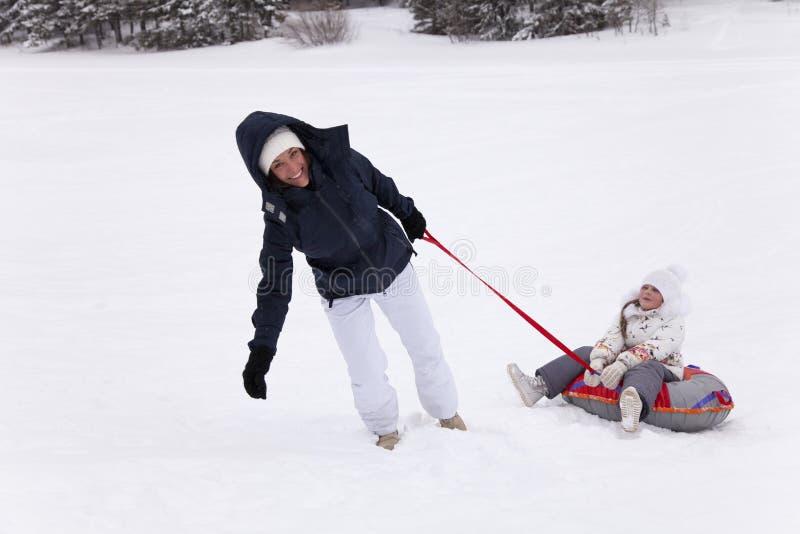 Счастливое ` s матери пробуя получить вверх по дочери холма сидя в sno стоковые фото