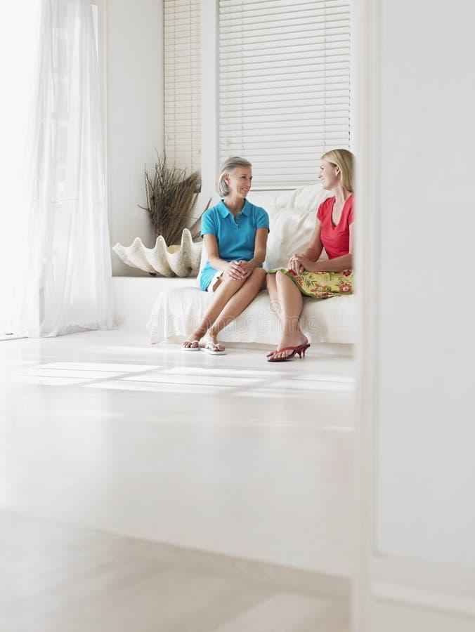 Счастливой женщины постаретые серединой сидя на софе стоковые фотографии rf