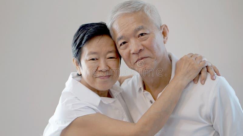 Счастливые азиатские старшие пары на белой предпосылке любят и обнимают стоковые фотографии rf