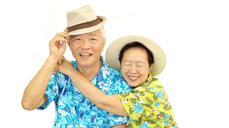 Счастливые азиатские старшие пары обнимая счастливо нося шляпу готовую для стоковое фото