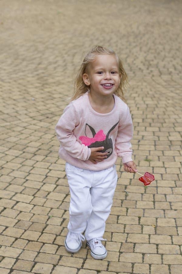 Счастливые бега девушки ребенка с конфетой стоковые фото