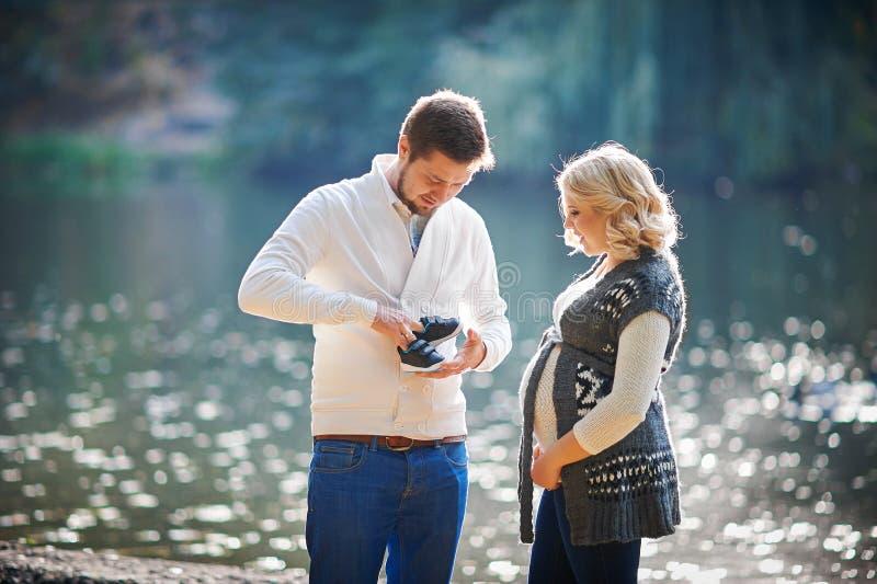 Счастливые беременные женщины и ее супруг во время прогулки с человеком около озера стоковая фотография rf