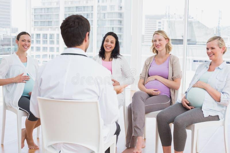 Счастливые беременные женщины слушая к доктору на антнатальном классе стоковое изображение