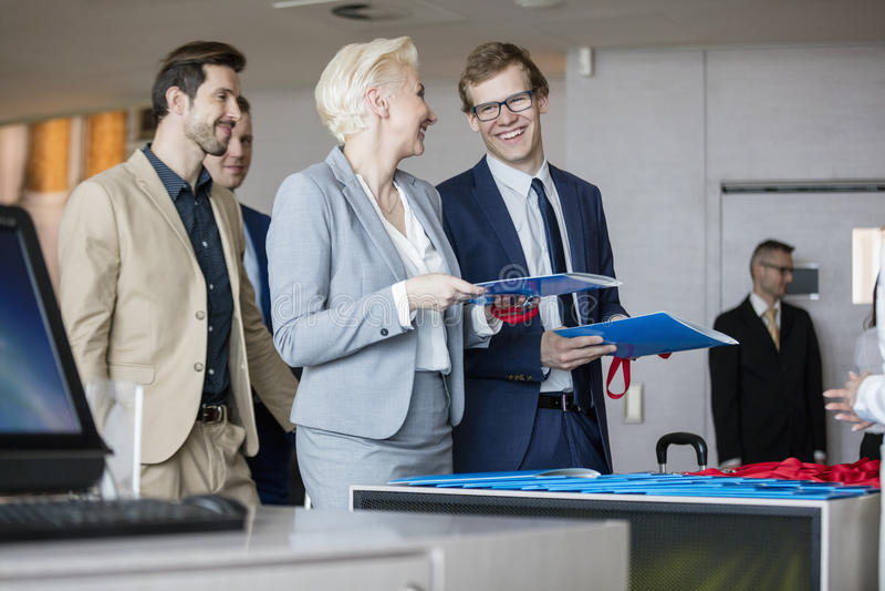 Счастливые бизнесмены говоря пока файлы удерживания на счетчике приема в выставочном центре стоковое фото