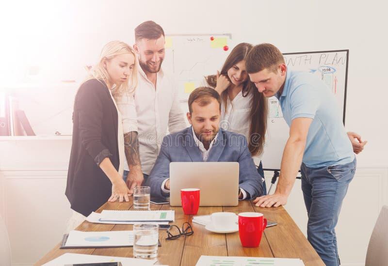 Счастливые бизнесмены команды вместе с компьтер-книжкой в офисе стоковая фотография rf
