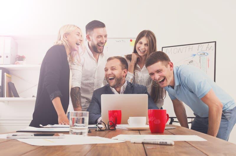 Счастливые бизнесмены объединяются в команду совместно имеют потеху в офисе стоковые фото
