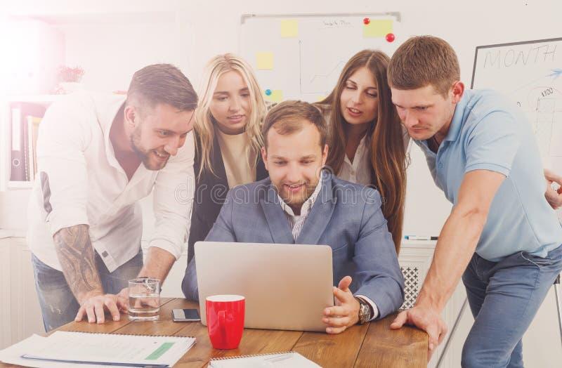 Счастливые бизнесмены объединяются в команду совместно около компьтер-книжки в офисе стоковое изображение
