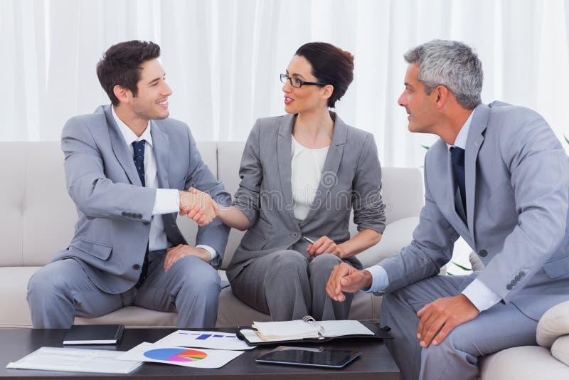 Счастливые бизнесмены работая и говоря совместно на софе стоковое изображение rf