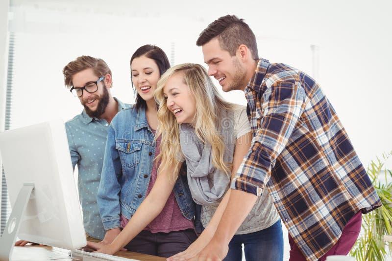 Счастливые бизнесмены работая на столе компьютера стоковое фото rf