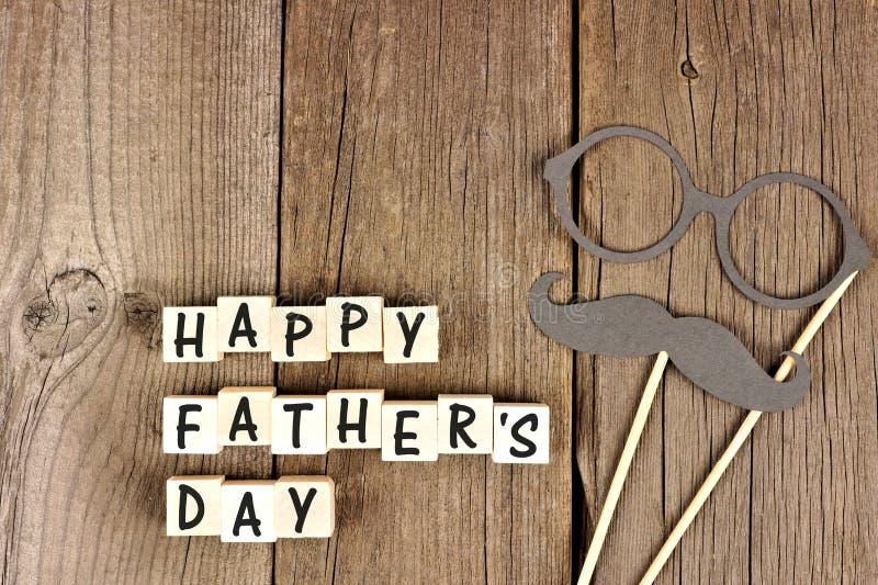 Счастливые блоки дня отцов с усиком и стеклами на древесине стоковые изображения