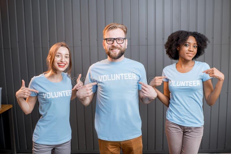 Счастливые волонтеры внутри помещения стоковое изображение rf