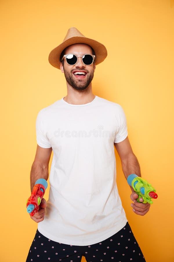 Счастливые водяные пистолеты игрушки удерживания молодого человека стоковое изображение