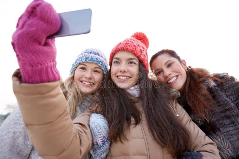 Счастливые девочка-подростки принимая selfie с smartphone стоковое фото