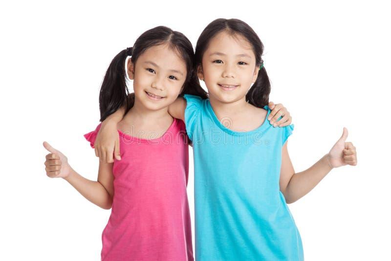Счастливые девушки близнецов азиата усмехаются большие пальцы руки выставки вверх стоковые фотографии rf