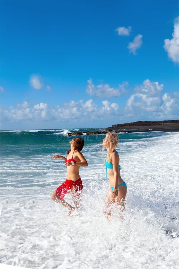 Счастливые девушки на пляже стоковая фотография rf