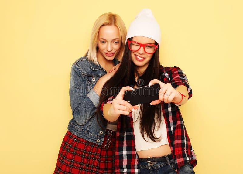 Счастливые девушки с smartphone над желтой предпосылкой Счастливая собственная личность стоковые изображения rf