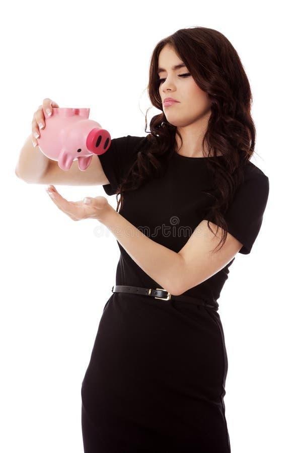 Счастливые деньги сбережений коммерсантки в piggybank стоковые изображения