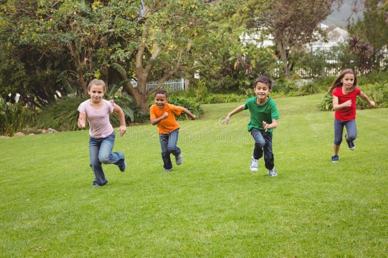 Счастливые дети бежать через траву стоковое изображение rf