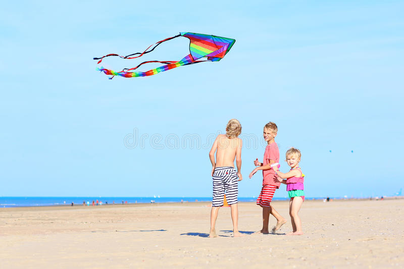 Счастливые дети летая змей на пляже стоковые изображения