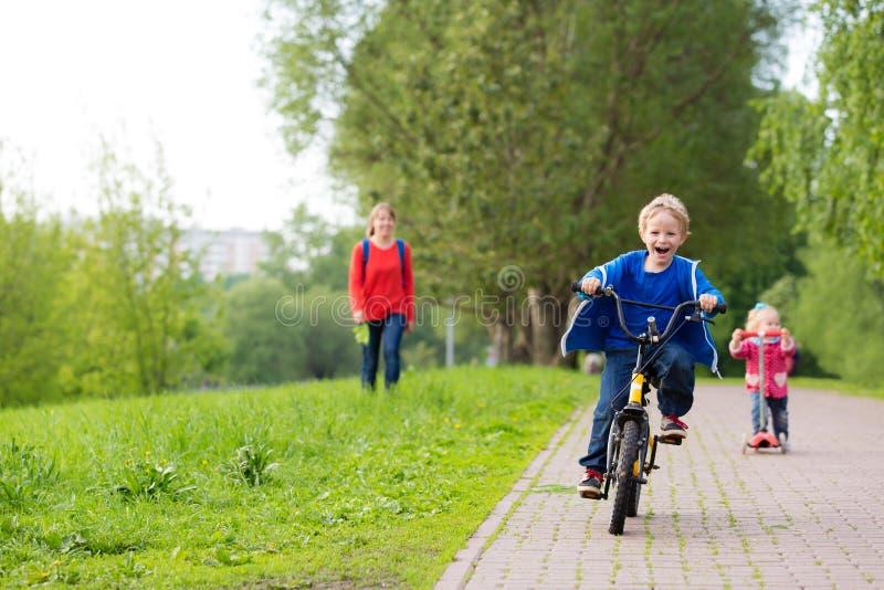 Счастливые дети ехать самокат и велосипед в парке стоковые фотографии rf