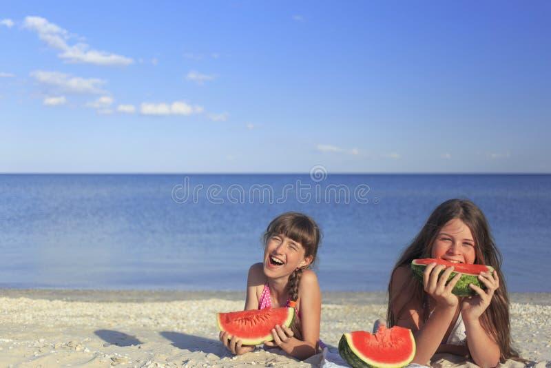 Счастливые дети на пляже есть сладостный арбуз стоковое фото