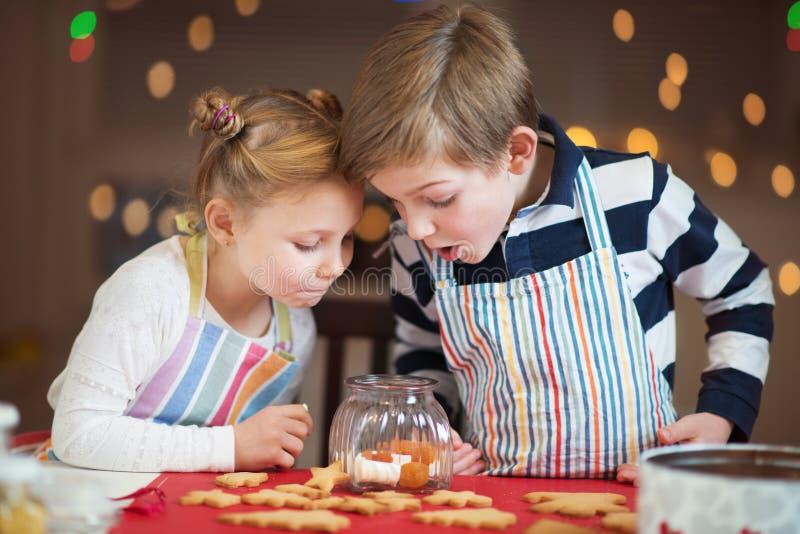 Счастливые дети подготавливая печенья на рождество и Новый Год стоковая фотография