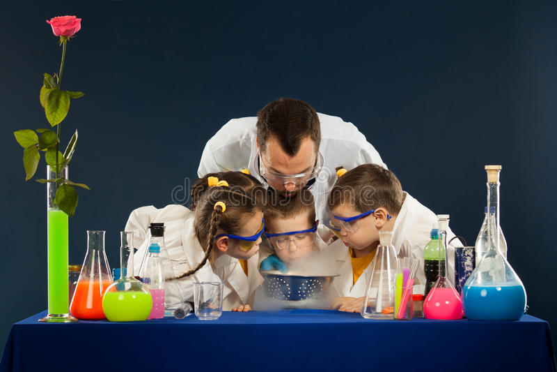 Счастливые дети при ученый делая науку экспериментируют в лаборатории стоковые изображения rf