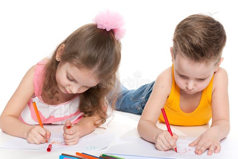 Счастливые дети рисуя на бумаге стоковые фотографии rf