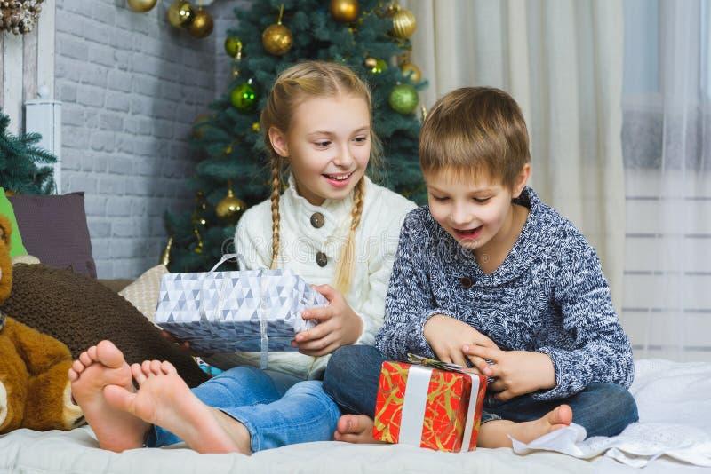 Счастливые дети сидя на кровати и держа подарки стоковые фотографии rf