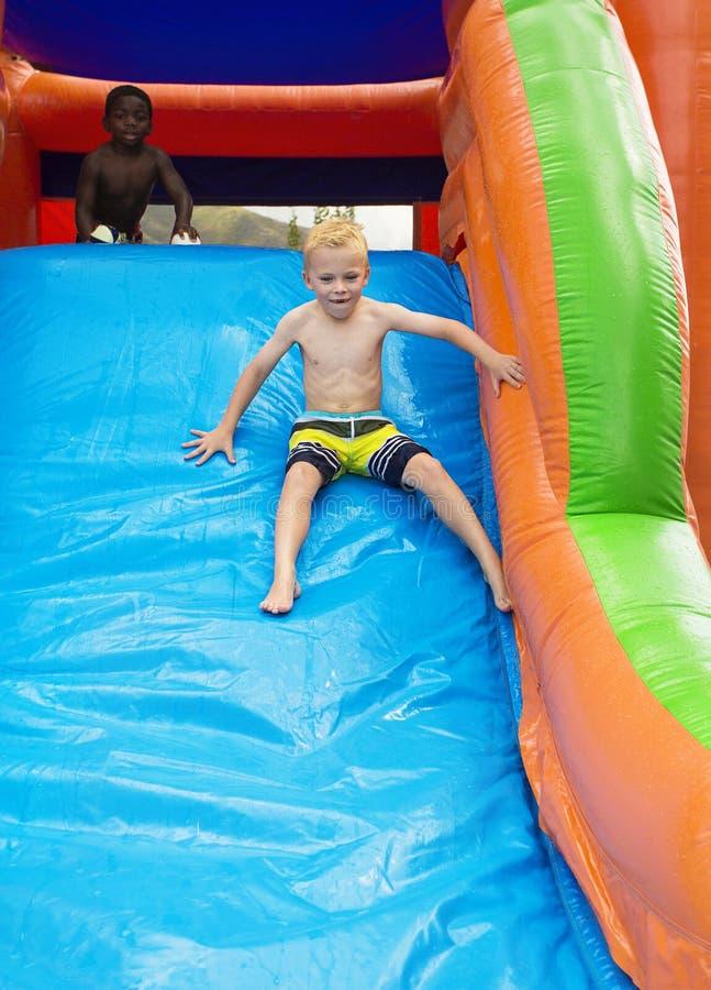 Счастливые дети сползая вниз с раздувного дома прыжока стоковое изображение