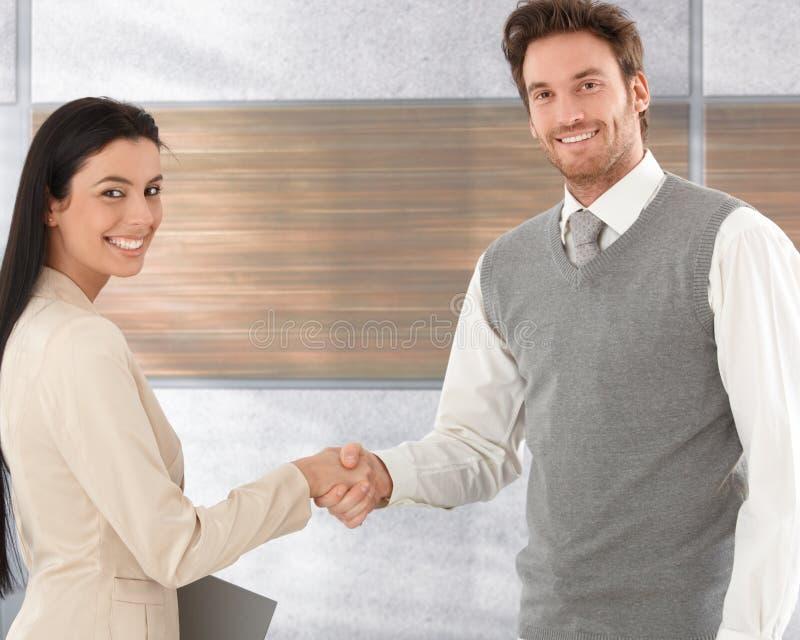Счастливые деловые партнеры тряся руки стоковые фото