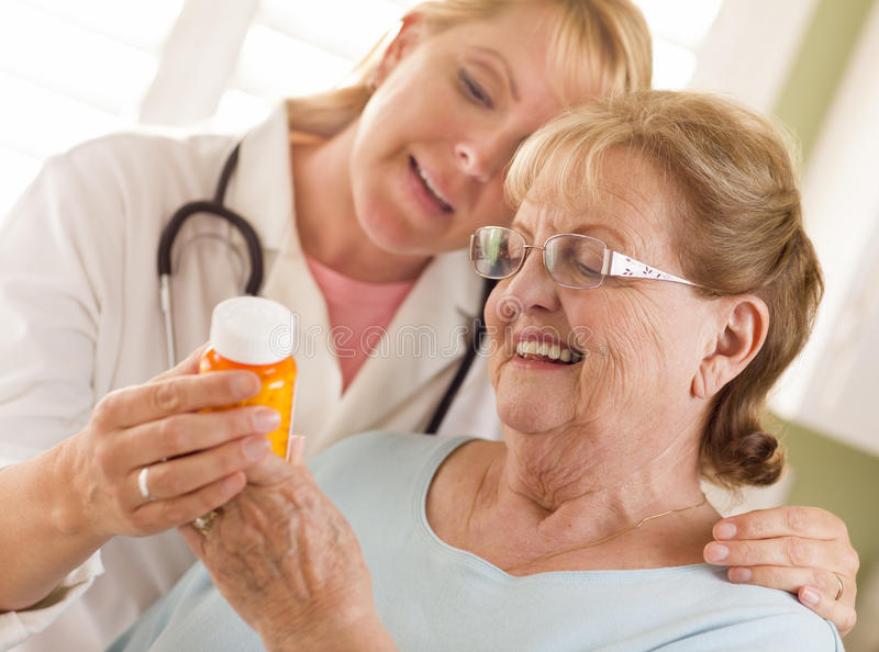 Женские доктор или нюна объясняя рецепт к старшему взрослому w стоковые фотографии rf