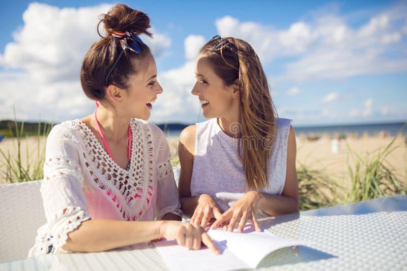 Счастливые женские друзья сидя на кафе ставят усмехаться на обсуждение друг к другу стоковые фотографии rf