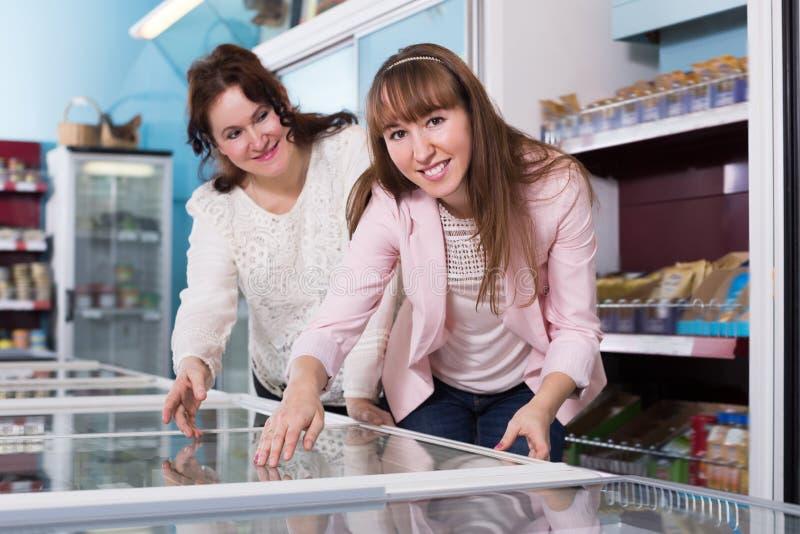 Счастливые женщины смотря в дисплее с замороженными продуктами стоковое фото rf