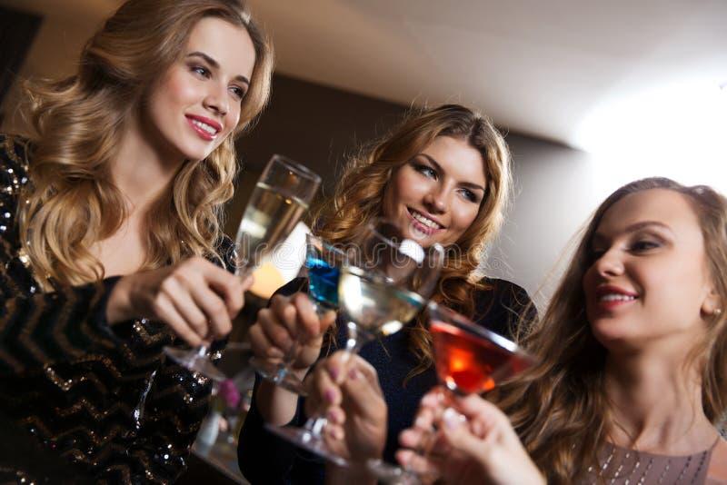 Счастливые женщины с пить на баре ночного клуба стоковая фотография