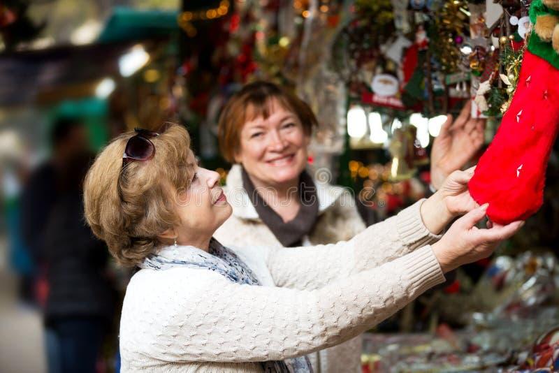 Download Счастливые зрелые женщины покупая украшения рождества Стоковое Фото - изображение насчитывающей снаружи, корабль: 81800380
