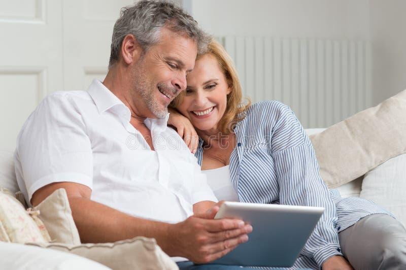 Счастливые зрелые пары с таблеткой стоковые фото