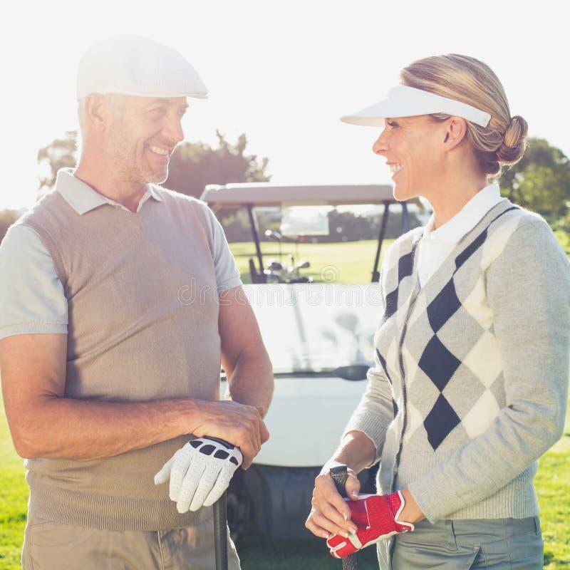 Счастливые играя в гольф пары беседуя с багги гольфа позади стоковая фотография