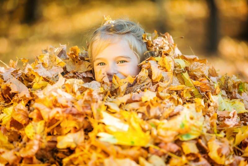 Счастливые игры маленькой девочки с листьями осени стоковое фото
