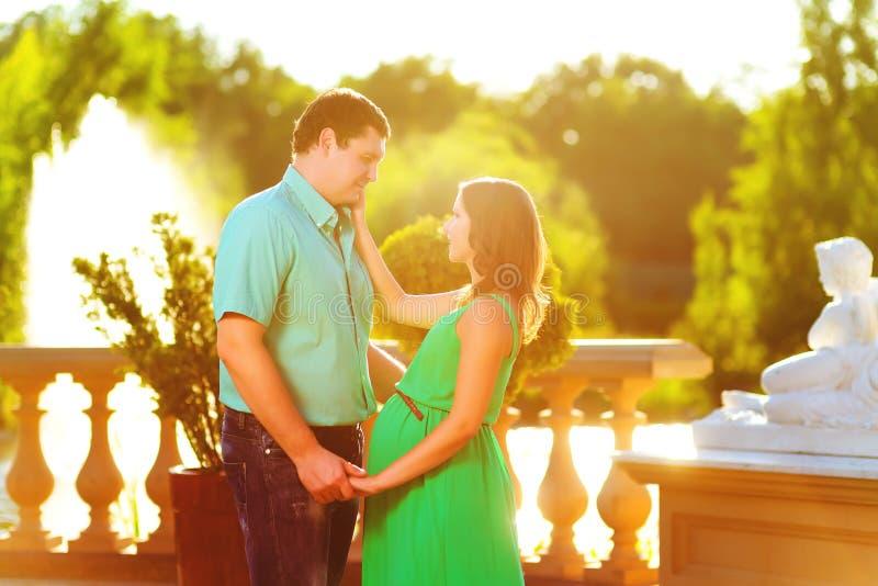 Счастливые и молодые беременные пары обнимая в природе стоковые изображения rf