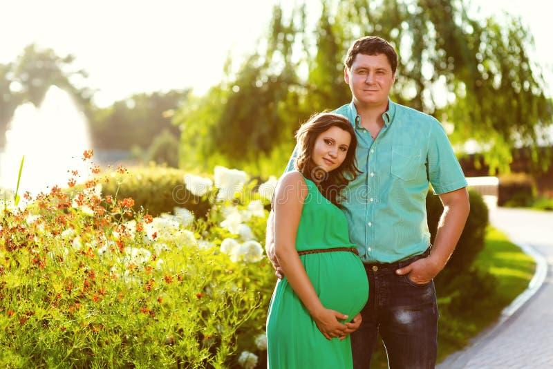 Счастливые и молодые беременные пары тонизированное изображение стоковые фото