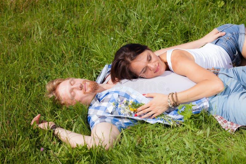 Счастливые красивые пары в влюбленности лежа на луге стоковая фотография rf