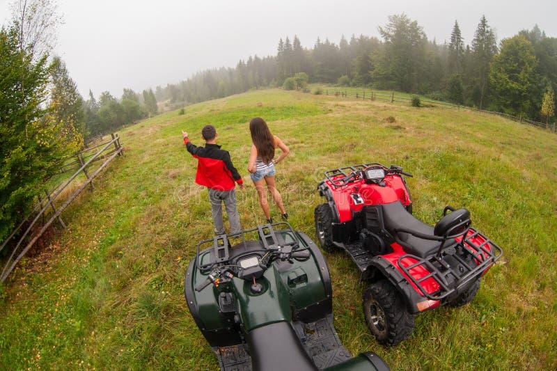 Счастливые красивые пары стоя близко 4-Уилеры ATV стоковое изображение