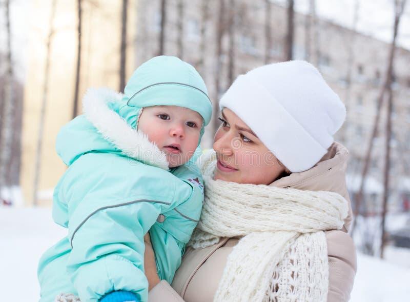 Счастливые мать и младенец семьи в парке в зиме стоковое изображение rf