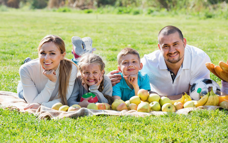 Счастливые мать и отец при 2 подростка лежа в саде стоковое фото