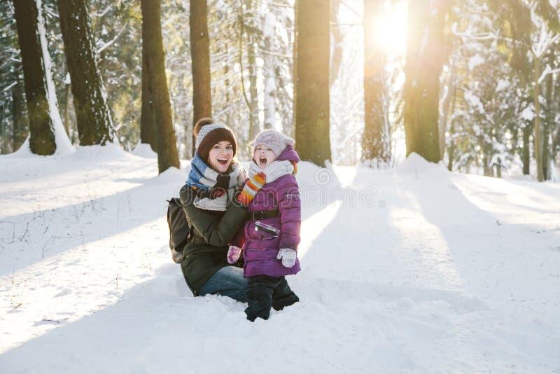 Счастливые мать и дочь в лесе зимы стоковые фото