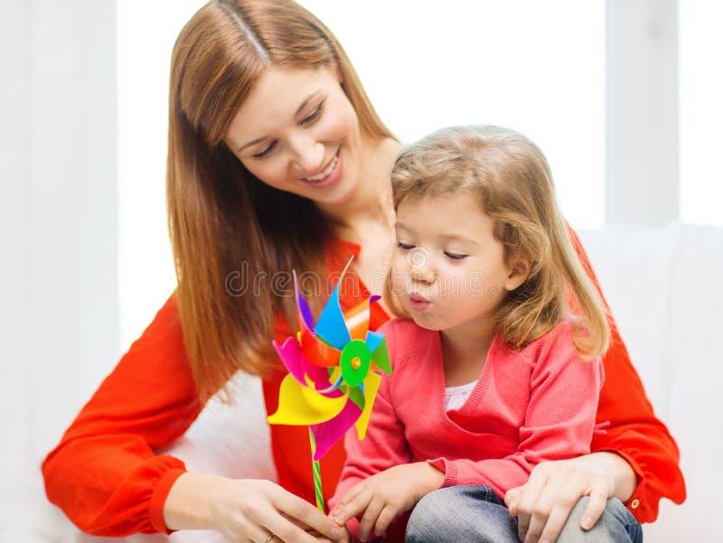 Счастливые мать и дочь с игрушкой pinwheel стоковые изображения rf