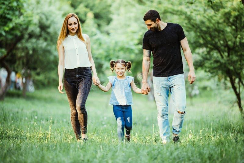 Счастливые мать, отец и маленькая девочка идя в лето паркуют стоковые изображения rf